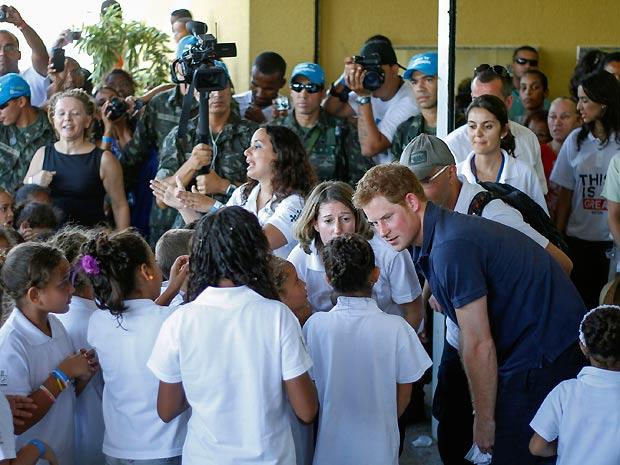 O príncipe Harry (à dir., de camisa azul), conversa com crianças durante visita a projeto social na comunidade Fazendinha, no Complexo do Alemão, no Rio de Janeiro, neste sábado (10) (Foto: Ide Gomes/AE)