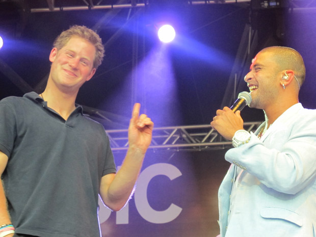 O príncipe Harry (à esq.) e o cantor Diogo Nogueira durante show do sambista no Conjunto de Favelas do Alemão: 'Como estão vocês?', perguntou a realeza britânica aos moradores da comunidade (Foto: Tássia Thum/G1)
