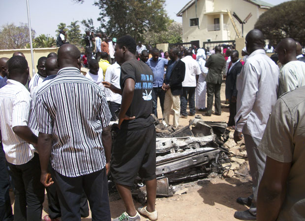 Pessoas se reúnem em torno de um carro usado por homem-bomba em uma igreja católica de Jos (Foto: AP)