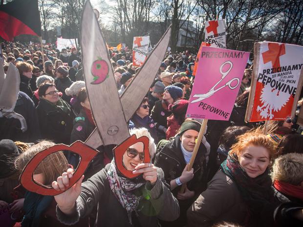 Feministas protestam com cartazes em passeata neste domingo (11), em Varsóvia, na Polônia (Foto: AFP/Wojtek Radwanski)