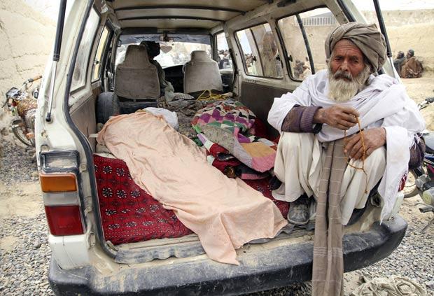 Homem permanece ao lado de corpo de afegão morto por soldado americano. (Foto: Allauddin Khan/AP)