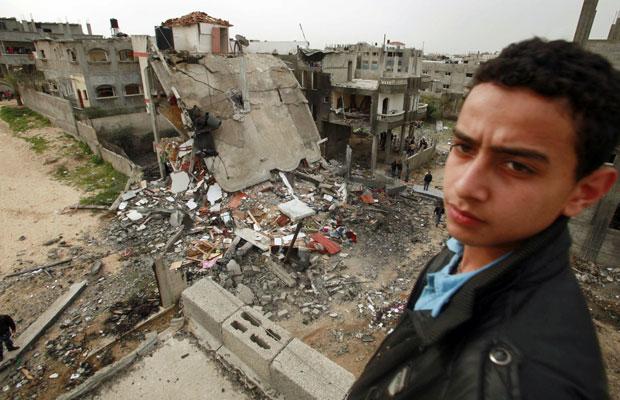 Jovem palestino fica em frente a prédio destruído após ataque israelense em Jabalya, norte da Faixa de Gaza, nesta segunda (12) (Foto: Suhaib Salem/Reuters)