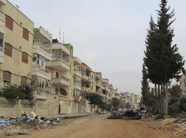Destruição provocada por forças de segurança em  Inshaat, bairro de Homs, vista neste domingo (11) (Foto: AP)