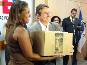 João da Costa entrega kit com 35 livros à professora. (Foto: Katherine Coutinho / G1)