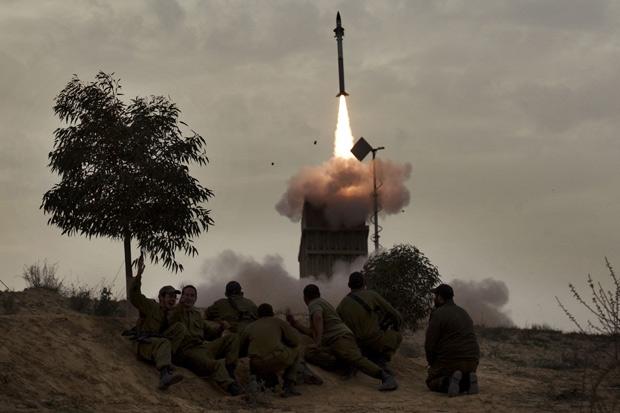 Soldados israelenses assistem a lançamento de míssil em na cidade de Beer Sheva, nesta segunda (12) (Foto: Menahem Kahana / AFP )