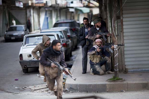 Rebeldes tomam posição durante confronto com forças do governo na cidade síria de Idlib neste domingo (11) (Foto: AP)