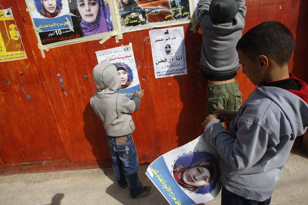 Crianças parentes da detida Hana Shalabi, pregam cartazes pedindo libertação dela em Birqin, na Cisjordânia, em fevereiro (Foto: Abed Omar Qusini / Reuters)