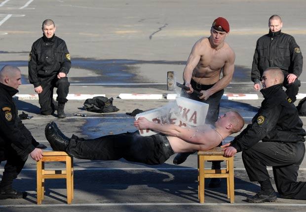 Soldado quebra blocos de concreto colocados sobre peito de colega. (Foto: Viktor Drachev/AFP)