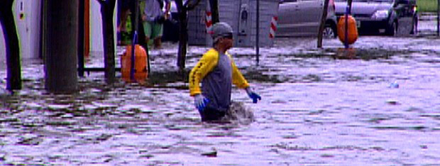 Homem atravessa a rua com água acima dos joelhos (Foto: Reprodução/RBS TV)