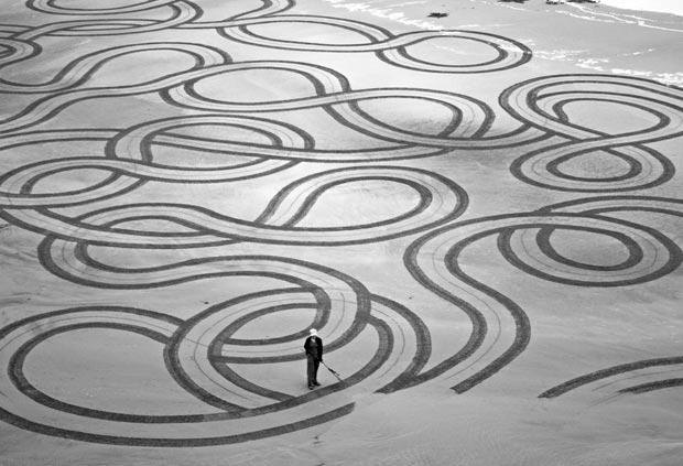 Artista americano faz 'desenhos gigantes' na areia da praia (Foto: Caters)