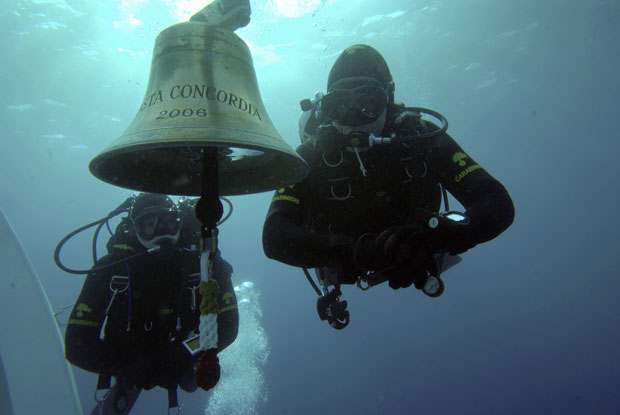 Mergulhadores da guarda costeira italiana aparecem com o sino do Costa Concordia durante operações de resgate de corpos ainda em janeiro, dias após o naufrágio (Foto: Reuters/Centro subacquei dei Carabinieri)