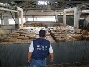 Funcionário da Receita observa mercadorias (Foto: Divulgação/Receita Federal)