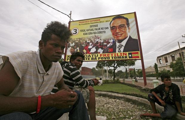 Timorenses sentados em frente a um poster de Francisco Guterres, candidato a presidente do Timor Leste, em Dili (Foto: Firdia Lisnawati / AP)