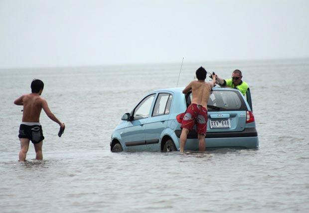 Turistas tiveram que abandonar veículo após ficarem presos em praia. (Foto: Chris McCormack/Redland Times/Reuters)