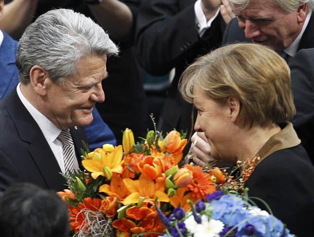 Joachim Gauck, novo presidente da Alemanha, recebe flores da chanceler Angela Merkel após sua vitória neste domingo (18) em Berlim (Foto: Reuters)