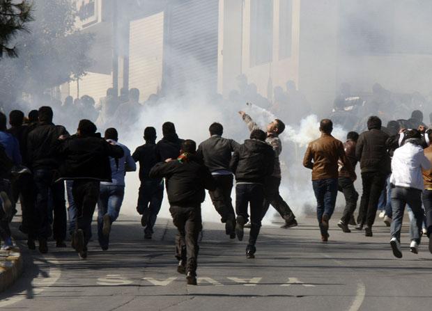 Manifestante joga bomba de gás lacromogênio lançada pela polícia durante protesto na Turquia (Foto: Umit Bektas/Reuters)