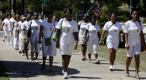 Integrantes do grupo dissidente Damas de Branco saem para sua marcha semanal em frente a igreja de Santa Rita em Havana, neste domingo (18) (Foto: Franklin Reyes / AP)