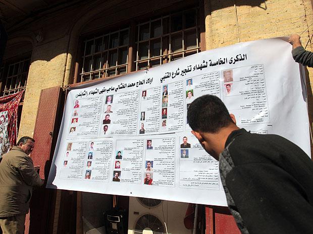 Iraquianos seguram um cartaz, em 5 de março de 2012, mostrando fotos das vítimas do atentado ocorrido há exatos cinco anos na rua Mutabani (Foto: Ali Al Saad/AFP)