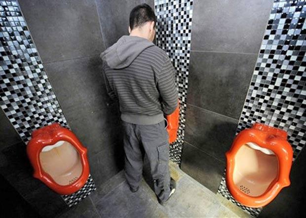 Homem usa toilete no restaurante Rosenmeer, na cidade alemã de Moenchenglad, em 2008. Os mictórios em forma de boca feminina criados pelo designer holandês Meike van Schijndel, foram criticados por serem considerados ofensivos às mulheres.  (Foto: AFP)