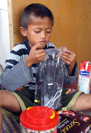 O menino Ilham, de 8 anos, é visto brincando em sua casa em Bogor (Foto: AFP/Komnas Perlingdungan)