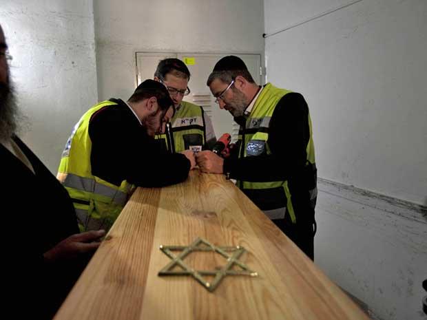 Funcionários israelenses preparam caixão de uma das vítimas de atirador que matou 4 pessoas em ataque na porta de uma escola em Toulouse, na França. (Foto: Oded Balilty / AP Photo)