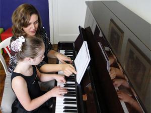 Lyvia com a professora de piano, Karina Gomes. (Foto: Alex Araújo/G1)