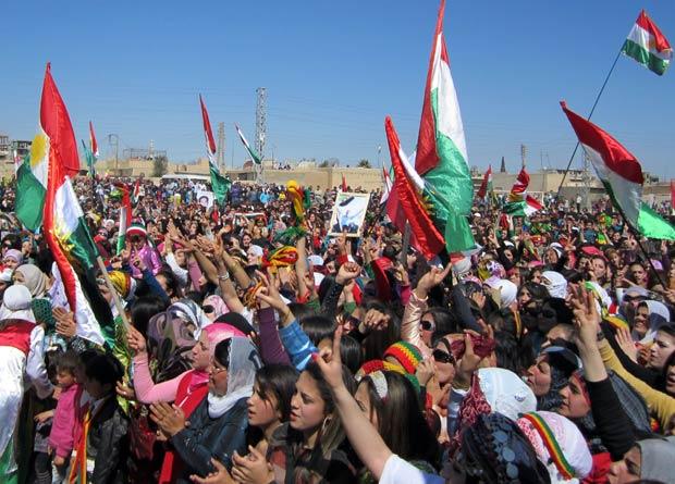 Sírios curdos tremulam bandeiras curdas em manifestação contra o governo em Qamishli, nesta terça (21)  (Foto: AFP)