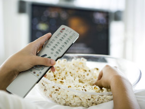 Telespectador come pipoca enquanto assiste TV (Foto: AFP)