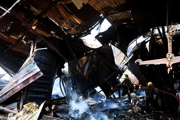 Restos do mercado incendiado nesta quinta-feira (22) na cidade indiana de Calcutá (Foto: AFP)