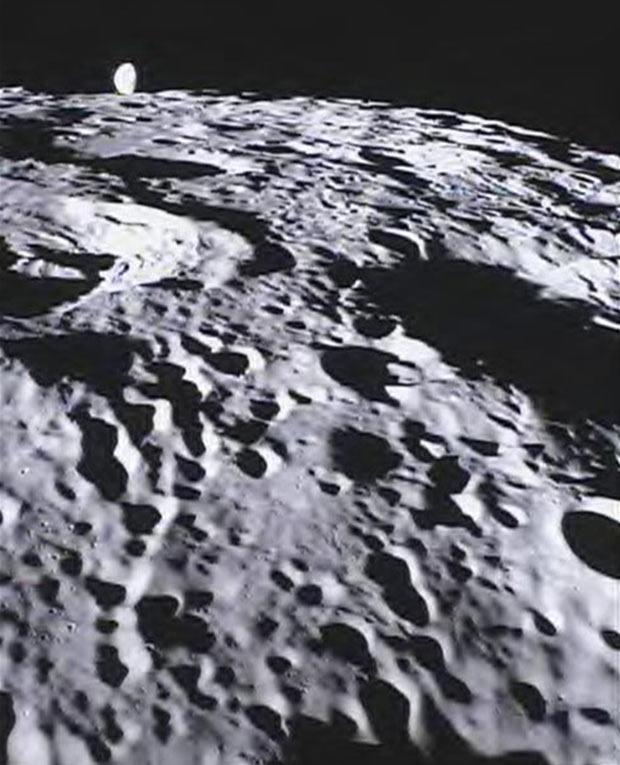 Imagem divulgada pela Nasa mostra de perto a superfície da Lua e, ao fundo, uma visão parcial da Terra. (Foto: Nasa/AP)