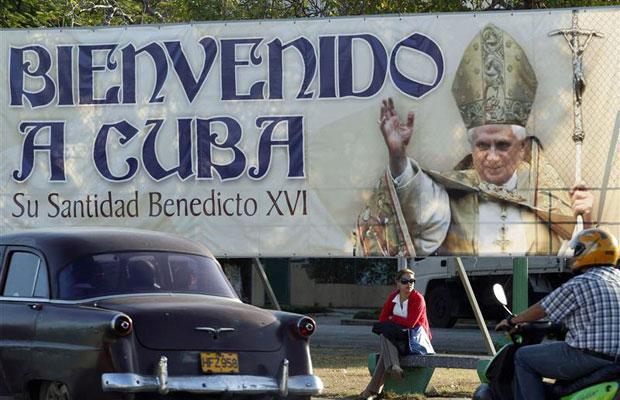 Mulher é vista sentada abaixo de cartaz do Papa Bento 16 em Havana (Foto: Enrique de la Osa/Reuters)