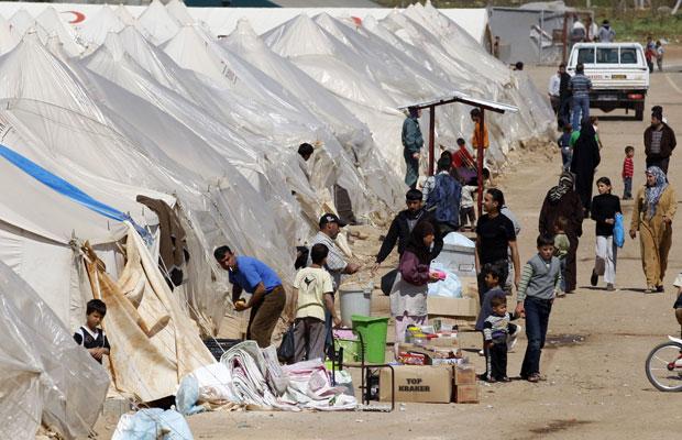 Refugiados sírios caminham pelo campo de Reyhanli, na fronteira com a Turquia (Foto: Osman Orsal/Reuters)