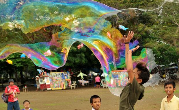 Criança brinca com a bolha gigante. Andrew Ang criou uma fórmula secreta de solução líquida e a vende no parque (Foto: Noel Celis/AFP)