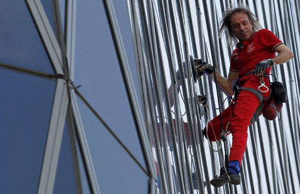 Alain Robert, conhecido como 'homem aranha' francês, ajusta equipamentos enquanto escala o Bakrie Tower, em Jacarta, na Indonésia (Foto: Supri/Reuters)