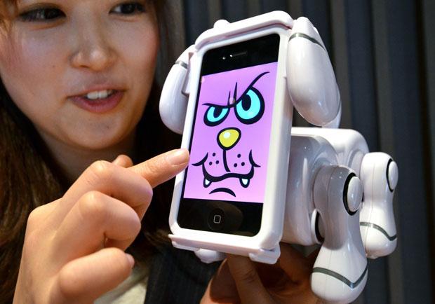 """A fábrica de brinquedos japonesa Bandai criou um suporte para iPhone e iPod touch no formato de brinquedo. Chamado de """"Smart Pet"""", o robô age como um bichinho virtual. Segundo o site """"Touch Arcade"""", ao baixar um aplicativo para o smartphone, o programa transforma a tela do aparelho no rosto de um animal virtual. O """"Smart Pet"""" ainda usa a câmera frontal do iPhone para reconhecer e reagir a gestos e expressões. (Foto: Yoshikazu Tsuno/AFP)"""