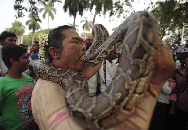Um indiano colocou a cabeça de uma cobra dentro de sua boca durante um festival hindu no domingo em Yangon, na Índia. (Foto: Reuters)