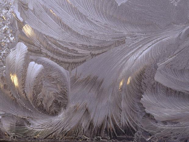 """Em uma noite fria de fevereiro na província canadense de Terra Nova, este padrão se formou em uma janela na casa de Helen Jones. """"Esta imagem em formato de pena apareceu quando o sol começou a nascer e brilhar através do gelo"""", disse ela. """"Eu precisei tirar esta foto imediatamente, porque não ia demorar muito até o gelo começar a derreter"""". (Foto: Helen Jones)"""