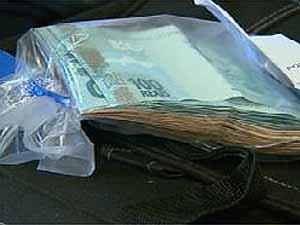 Dinheiro apreendido com mulher de suspeito de roubar R$ 260 mil em banco de Ribeirão (Foto: Reprodução EPTV)