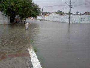 Moradores atravessam ruas alagadas (Foto: Alcides Lima/G1 CE)