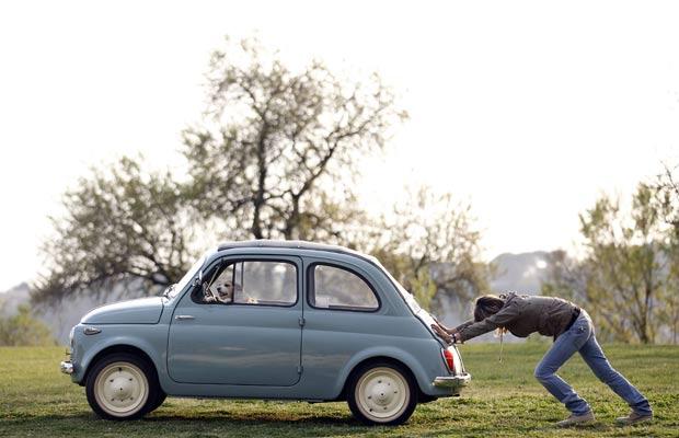Mulher foi flagrada empurrando seu carro em um bairro de Roma. (Foto: Alessandro Bianchi/Reuters)
