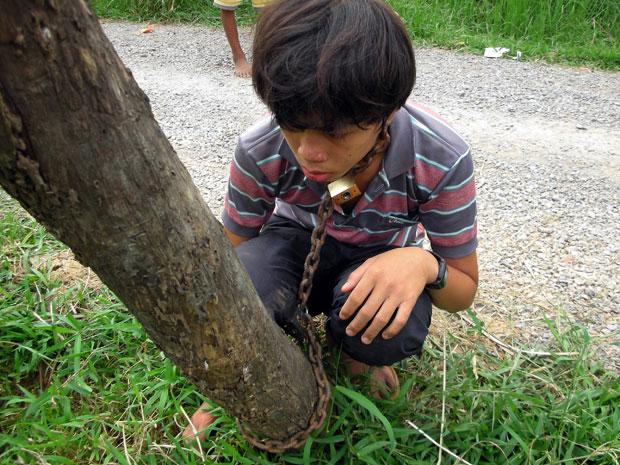 Jovem cambojano foi acorrentado pelo pai a um poste de energia elétrica como forma de castigo (Foto: AFP)