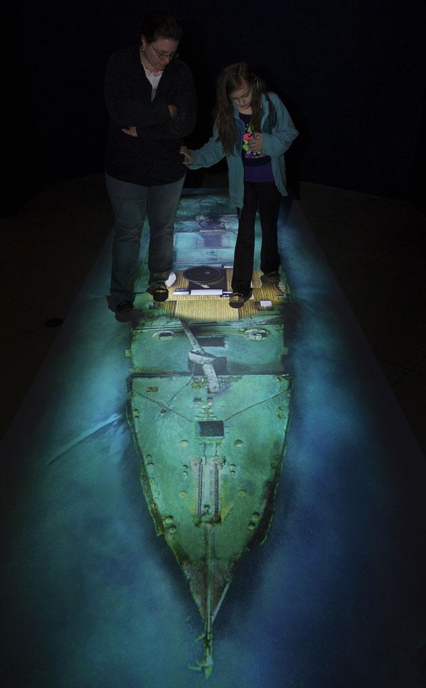 """O museu da """"National Geographic"""" em Washington D.C., nos Estados Unidos, abriu ao público nesta quinta-feira (29) a exposição """"Titanic: 100 anos de obsessão"""". A mostra possui artigos como um piso interativo, que mostra a estrutura do navio naufragado vista de cima e, quando um visitante caminha sobre ele, pode ver como era a estrutura no passado. (Foto: Paul J. Richards/AFP)"""