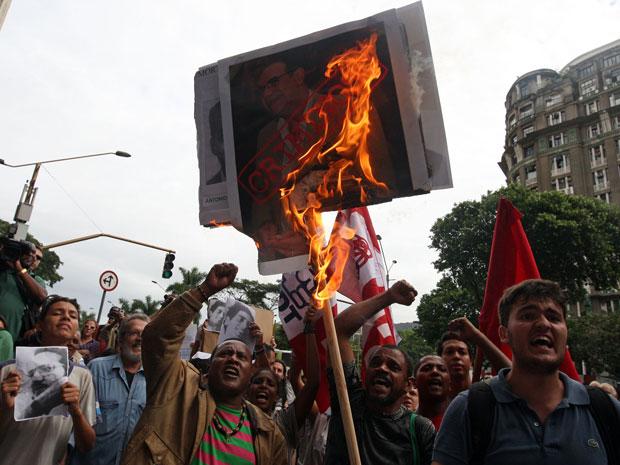 Manifestantes queimam cartaz em protesto no Centro do Rio (Foto: Fábio Motta/AE)