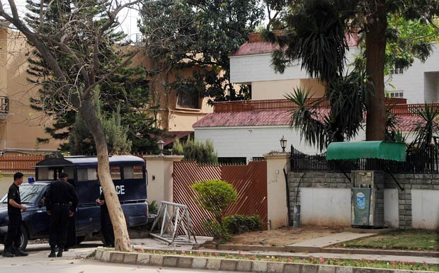 Policiais paquistaneses montam guarda na casa em que acredita-se que estejam sendo mantidos os parentes de Osama bin Laden, nesta sexta-feira (30), em Islamabad (Foto: AFP)