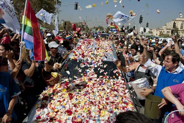 Milhares de pétalas cobrem carro com caixão durante cortejo fúnebre de Daniel Zamudio, de 25 anos, que foi espancado até a morte em Santiago (Foto: Claudio Santana / AFP)