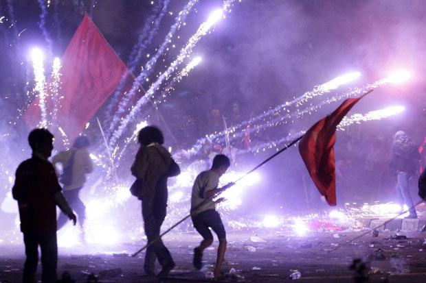 Manifestantes correm dos fogos de artifício usados pelos guardas (Foto: Achmad Ibrahim/AP)