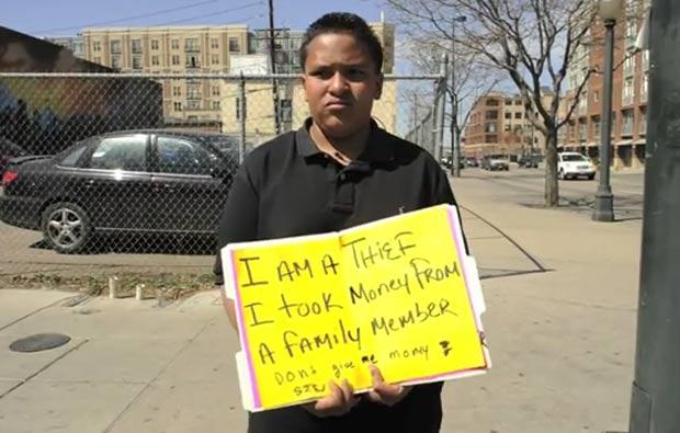 Adolescente seguea cartaz 'Eu sou um ladrão. Eu peguei dinheiro de um membro da família'. (Foto: Reprodução)