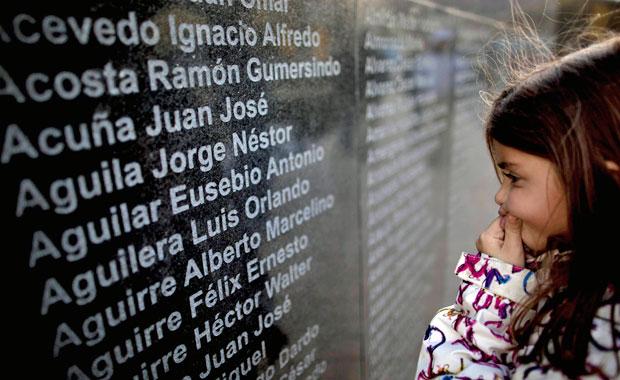 Menina lê os nomes dos soldados arentinos mortos na guerra de 1982, em monumento de Ushuaia (Foto: Natacha Pisarenko/AP)