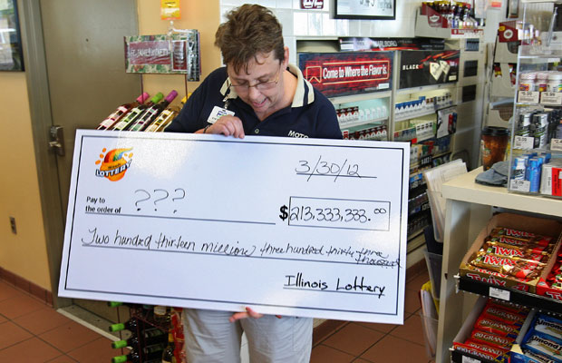 Gerente da loja Moto Mart, em Illinois, olha para cheque gigante dado pela Loteria ao comprovar que um dos bilhetes ganhadores foi vendido pela loja (Foto: AP)
