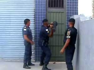Guarda precisou utilizar uma marreta para arrombar uma das portas de ferro do prédio (Foto: Reprodução EPTV)
